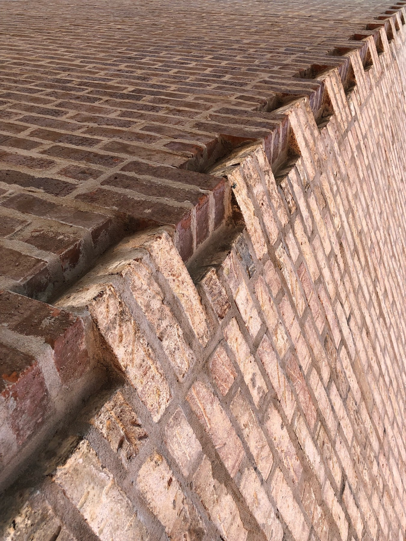 Two brick walls joined together in a teeth-like manner.  The joint is angled from bottom left to top right, and the wall on the right is a lighter shade of red than the left.