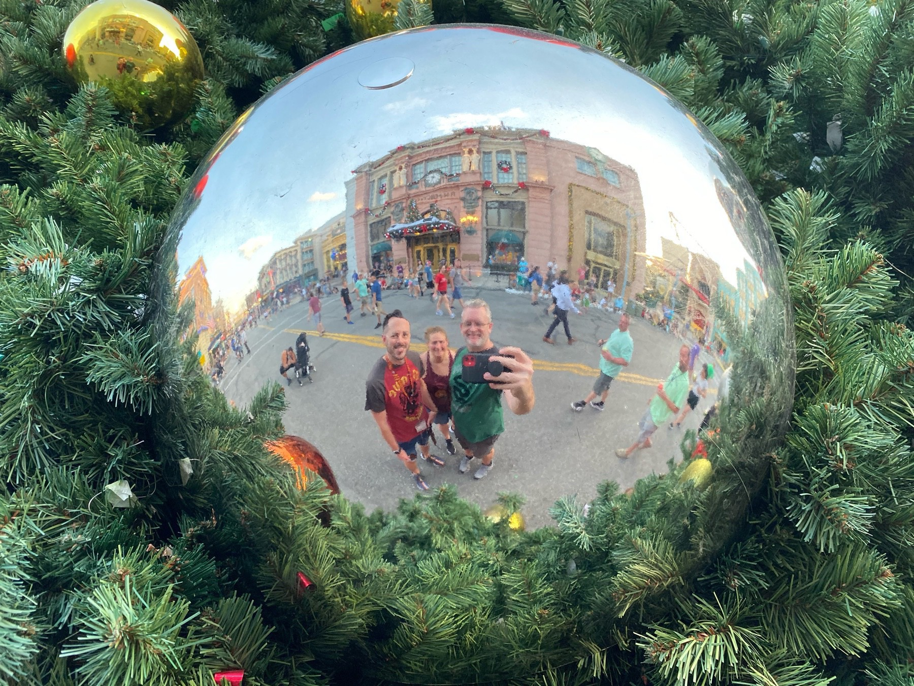 A group of three people (one female and two males) take a photo of their reflection in a giant, silver Christmas tree ornament with buildings in the background.