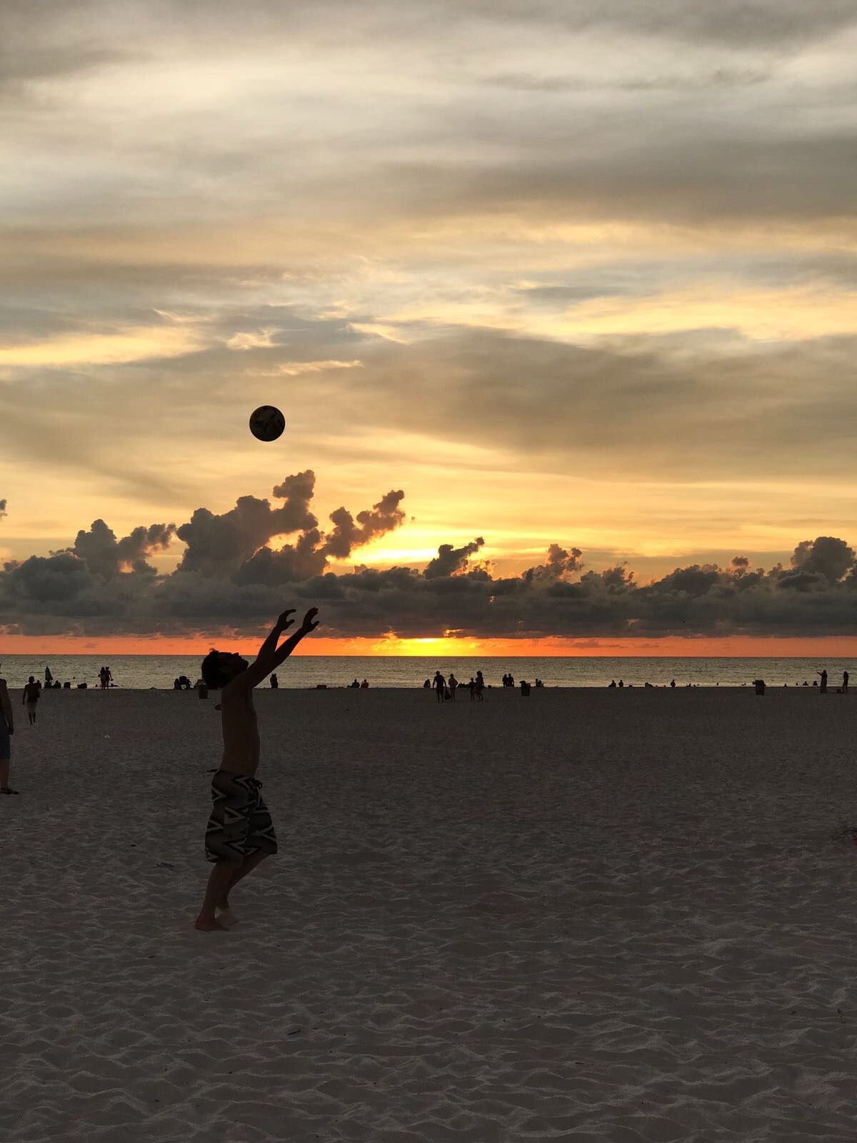 A sunset silhouette of a young male volleyball player tossing the volleyball high above his head